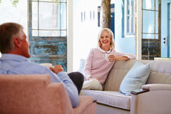 Mature Couple At Home Relaxing In Lounge With Hot Drink Stock Image