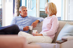 Mature Couple At Home Relaxing In Lounge With Hot Drink Stock Photo