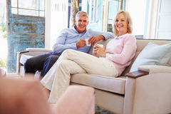 Mature Couple At Home Relaxing In Lounge With Hot Drink Stock Images