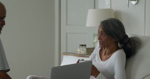 Mature couple at home. Side view of a mature mixed race couple with a laptop computer sitting on a bed at home talking stock video