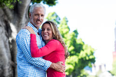 Mature couple hugging against tree. Portrait of romantic mature couple hugging against tree in city Stock Photography