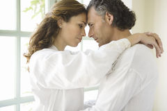Mature Couple hugging by garden doors. Royalty Free Stock Photography