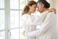 Mature Couple hugging by garden doors. Royalty Free Stock Image
