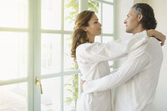 Mature Couple hugging by garden doors. Royalty Free Stock Photo