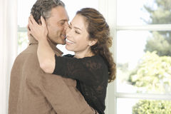 Mature couple hugging in living room. Stock Photography