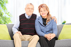 Mature couple hugging seated on sofa at home Royalty Free Stock Photography