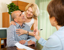 Mature couple with insurance agent. Friendly  mature couple discussing details of private insurance with agent Stock Photography