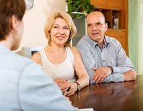 Mature couple with insurance agent. Positive mature couple discussing details of private insurance with agent Royalty Free Stock Photos