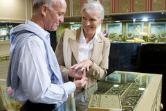Mature couple in jewelery shop, woman trying on ring, smiling Stock Image