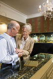 Mature couple in jewelery shop, woman trying on ring, smiling Stock Photos