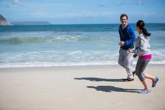 Mature couple jogging on beach Stock Photo