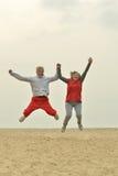 Mature couple jumping on beach Stock Image