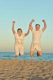 Mature couple jumping on beach Royalty Free Stock Image