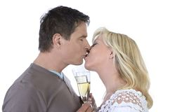 Mature couple kissing with glasses of champagne Stock Photography
