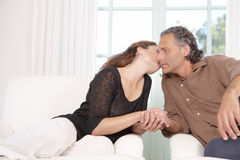 Mature couple kissing in living room. Stock Photography