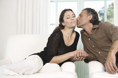Mature couple kissing in living room. Stock Photo