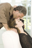 Mature couple kissing in living room. Stock Photos