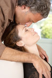 Mature couple kissing in living room. Royalty Free Stock Images