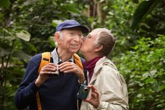 Mature Couple Kissing in Woods Royalty Free Stock Image