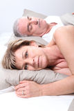 Mature couple laid in bed Royalty Free Stock Photography