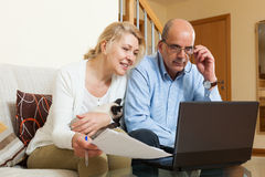 Mature couple with laptop in home Royalty Free Stock Photos