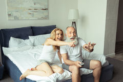 Mature couple laughing and pointing on tv while sitting on bed at home royalty free stock image