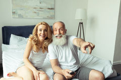 Mature couple laughing and pointing on tv while sitting on bed at home. Happy mature couple laughing and pointing on tv while sitting on bed at home Stock Photography
