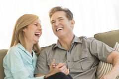 Mature Couple Laughing Together On Sofa At Home Royalty Free Stock Images