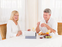 Mature couple laughing and video chatting with a tablet as they eat healty breakfast. Attractive lively mature couple laughing in video chat with relatives on Royalty Free Stock Photo