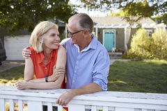 Mature Couple Leaning On Back Yard Fence Royalty Free Stock Photography
