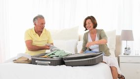 Mature couple leaving for vacacion and packing Royalty Free Stock Photo