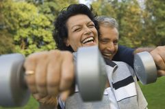 A mature couple lifting dumbbells Stock Photography