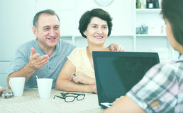 Mature couple listening to woman with laptop Stock Images