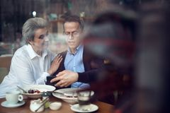 Mature couple look with interest in mobile phone. Enjoyable meetings. Waist up portrait of elegant mature men and women looking on something at mobile phone stock image