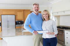 Mature Couple Looking Around Kitchen Of House For Sale Royalty Free Stock Photography