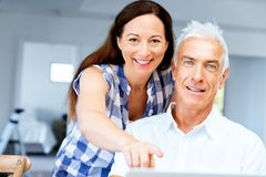 Mature couple looking at camera. Happy smiling mature couple at home Stock Image