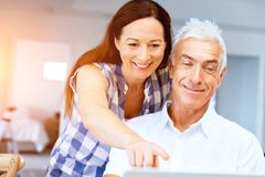 Mature couple looking at camera. Happy smiling mature couple at home stock photos