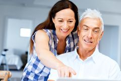 Mature couple looking at camera. Happy smiling mature couple at home royalty free stock images