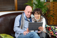 Mature couple looking at a digital tablet Royalty Free Stock Image