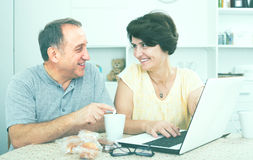 Mature couple looking on laptop at home Stock Photos