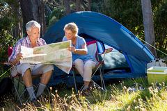 Mature couple looking map. On their camp site on the wood stock images