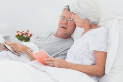 Mature couple looking at a newspaper Stock Photos
