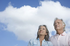 Mature Couple Looking Up Against Sky. Closeup low angle view of a mature couple looking up against sky Stock Image