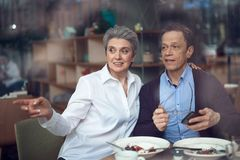 Mature couple looking from window of cafe. Enjoyable meetings. Waist up portrait of happy elegant aged men and women looking with surprise and interest on royalty free stock photo