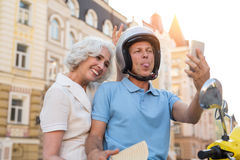 Mature couple looks at phone. Man in helmet shows tongue. Funny photo from the trip. On tour through Europe royalty free stock image