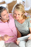 Mature couple in love sitting on sofa at home Stock Photo