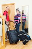 Mature couple with luggage   going on holiday. Positive mature couple with luggage in home going on holiday Royalty Free Stock Photos