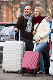 Mature couple with luggage at street. Happy mature couple with luggage standing at street and smiling Royalty Free Stock Photo