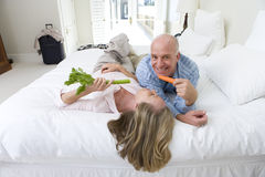 Mature couple lying on bed holding carrot and celery sticks, smiling, elevated view Stock Photography