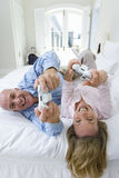 Mature couple lying on bed holding computer game controls, smiling, portrait, elevated view Royalty Free Stock Image